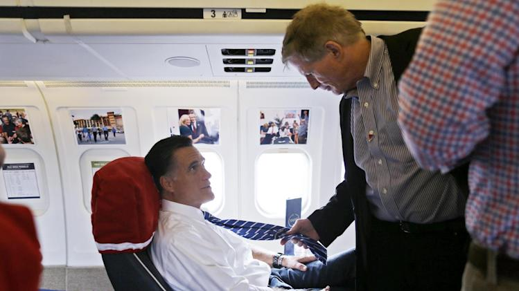Chief strategist Stuart Stevens, right, examines the necktie of Republican presidential candidate and former Massachusetts Gov. Mitt Romney after they boarded his campaign plane at Tampa International Jet Center, in Tampa, Fla., Sunday, Oct. 28, 2012. Romney was traveling to Ohio for campaign events with his vice presidential running mate Rep. Paul Ryan, R-Wis. (AP Photo/Charles Dharapak)