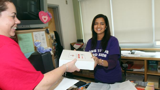 Shalini Regan, and 8th grade math teacher accepts an apple pie in honor of Pi Day (March 14, or 3.14) courtesy of Raytheon Company.  Recognition of Pi Day is a  part of the company's MathMovesU® initiative that encourages kids to pursue careers in the science, technology, engineering and math fields.  (Aynsley Floyd/AP Images for Raytheon Company)