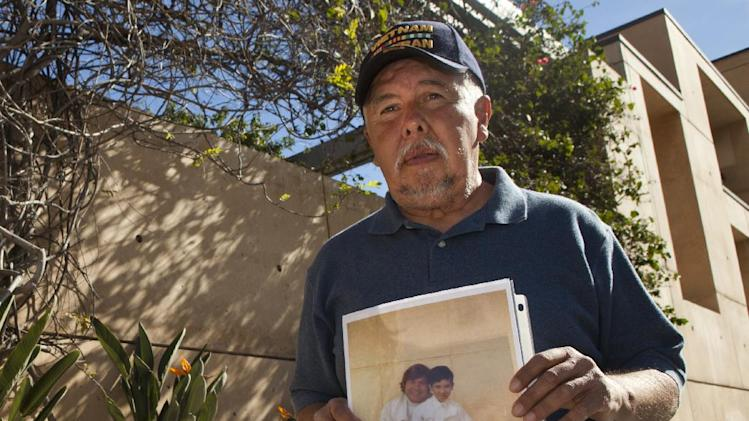 Frank Zamora, 67, holds an old photo of his son Dominic Zamora, then 8, sitting on the lap of his abuser, priest Michael Stephen Baker, as Zamora joins members the Survivors Network of those Abused by Priests (SNAP) during a news conference outside the Cathedral of Our Lady of the Angels in Los Angeles Monday, Feb. 1, 2013. Cardinal Roger Mahony of the largest Roman Catholic archdiocese in the United States was stripped of his duties in an unprecedented move by his successor Archbishop Jose Gomez, who described the church's actions during the growing sex abuse scandal as evil.  (AP Photo/Damian Dovarganes)
