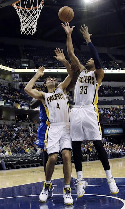 Indiana Pacers forward Danny Granger (33) pulls down a rebound in front of teamate Luis Scola (4) during the first half of an NBA preseason basketball game against the Dallas Mavericks in Indianapolis