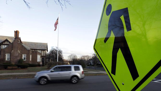 In this Dec. 27, 2013, photo a vehicle drives in front of Forest Avenue Elementary School in Glen Ridge, N.J. A presidential commission appointed by President Barack Obama is grappling with concerns that some schools no longer want to serve as polling places amid security concerns since the shooting in Newtown, Conn. Among those schools that have closed to balloting is Forest Avenue Elementary School. (AP Photo/Julio Cortez)