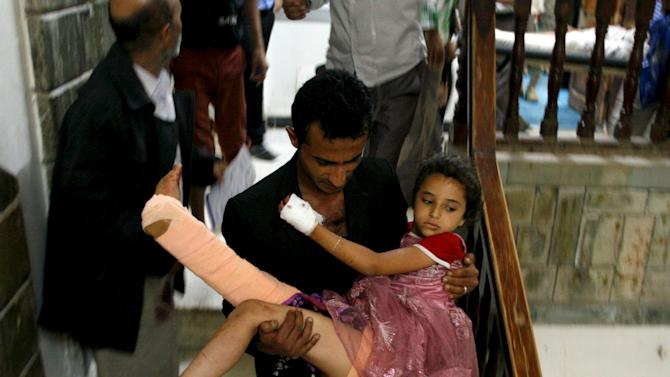 A man carries his sister after she recieved treatment at a hospital in Yemen's southwestern city of Taiz