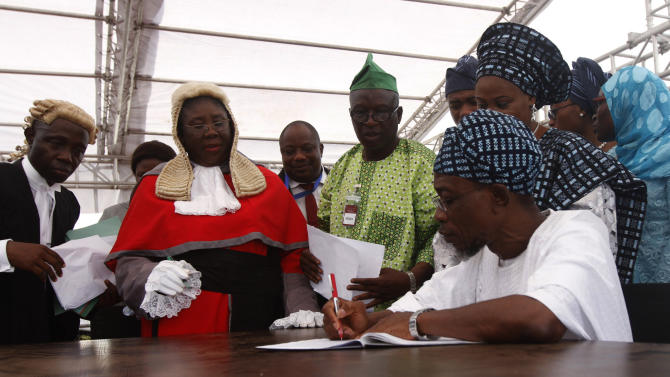 Osun state Governor Ogbeni Rauf Aregbesola signs the oath of office during his inauguration for second term in office in Osogbo