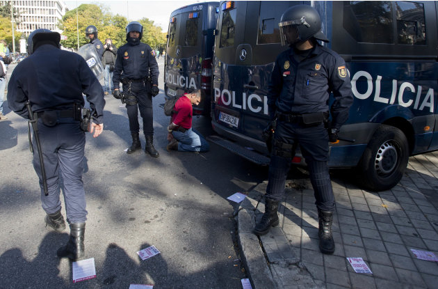 A man kneels down handcuffed next to police vans after being detained by the police during a general strike in Madrid, Wednesday Nov. 14, 2012. A Spanish Interior Ministry official says 32 people have