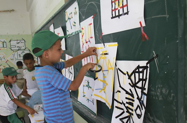 In this Wednesday, July 11, 2012 photo, Palestinian boys make drawings at a summer camp run by Hamas inside a school in Al-Qarara near Khan Younis, southern Gaza Strip. Since taking over Gaza five years ago, Hamas has competed with a U.N. agency for the hearts of Palestinian children. Each side ran summer camps, with Hamas featuring lessons in Islam and political indoctrination and the U.N. offering sports and games. Hamas has now won by default _ the U.N. canceled its camps this year because of a drop in donations.(AP Photo/Adel Hana)