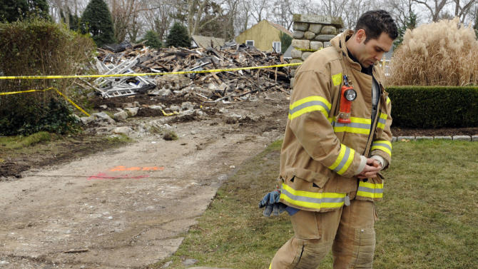 Stamford firefighter Nick Tamburro pays respect outside the home of Madonna Badger in Stamford, Conn., Tuesday, Dec. 27, 2011.  A fire at the home on Christmas morning killed Badger's three daughters and parents. The Christmas Day fire that killed three children and their grandparents was a tragic accident related to a fireplace in the home, not the result of foul play, Stamford Mayor Michael Pavia said Tuesday, Dec. 27, 2011. (AP Photo/Jessica Hill)