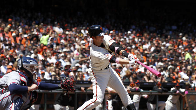 San Francisco Giants' Buster Posey, right, hits a single against the Atlanta Braves during the first inning of a baseball game in San Francisco, Sunday, May 12, 2013. (AP Photo/Tony Avelar)