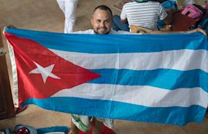 A Cuban deploys a Cuban flag in a shelter in the town…