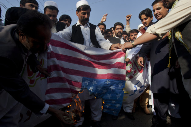 Members of the Azad Welfare Society burn a replica U.S. flag during a rally to condemn NATO airstrikes on Pakistani troops, Sunday, Dec. 4, 2011 in Rawalpindi, Pakistan. Pakistan is refusing to participate in the U.S. investigation of last week's NATO airstrikes along the Afghanistan border that killed 24 Pakistani soldiers. (AP Photo/Anjum Naveed)