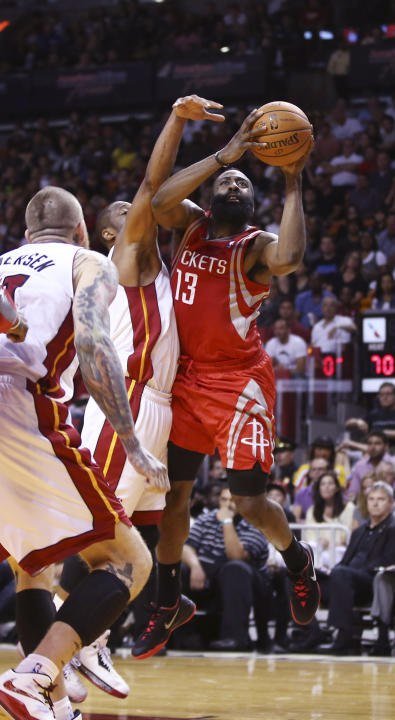 Miami Heat players Chris Andersen (11) and Dwyane Wade (3) try to block Houston Rockets' James Harden ((13) during the second half of an NBA  basketball game in Miami, Sunday, March 16, 2014. The