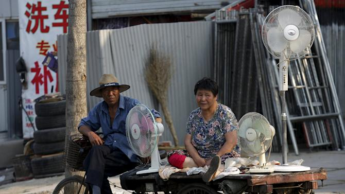 Vendors selling secondhand electric fans wait for customers at a market in  a village for migrant workers in Beijing