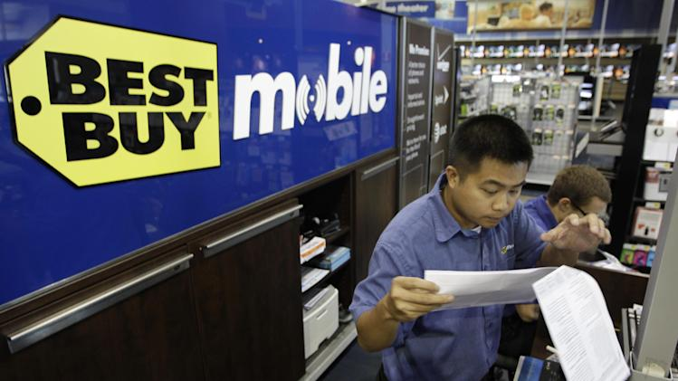 FILE - In this Sept 12, 2011 file photo, a Best Buy employee looks over a cell phone contract for a customer at a Best Buy in Mountain View, Calif. Best Buy Co.'s fiscal first-quarter profit dropped 26 percent on restructuring charges as the struggling electronics retailer began implementing its turnaround plan. Its adjusted earnings and revenue both topped Wall Street's expectations. (AP Photo/Paul Sakuma, File)