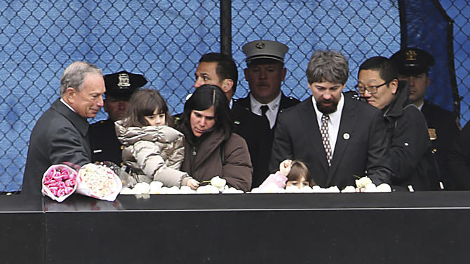 "New York City Mayor Michael Bloomberg, left, joins Stephen Knapp Jr., right, and his family as they lay flowers during a ceremony to honor the six people who died 20 years ago in the first terrorist attack on the World Trade Center, Tuesday, Feb. 26, 2013 in New York. Knapp's father, Stephen Knapp, was killed in the bombing. About 50 people attended the ceremony, held at the 9/11 memorial, where the twin towers were destroyed eight years later. The moment of silence was observed at 12:18 p.m., the time when a truck bomb was detonated below the north tower. The victims' names were read by family members before bagpipers played ""Amazing Grace.""  (AP Photo/Mary Altaffer)"