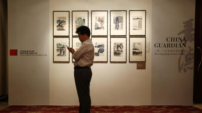 A Chinese collector looks at his mobile phone during the autumn sale of China Guardian Auctions Co., in Hong Kong Sunday, Oct. 7, 2012. Chinese and international auction houses are encroaching on each other's territory in Hong Kong and Beijing for the first time this autumn sale season as they step up the battle for the Asian art market. (AP Photo/Vincent Yu)