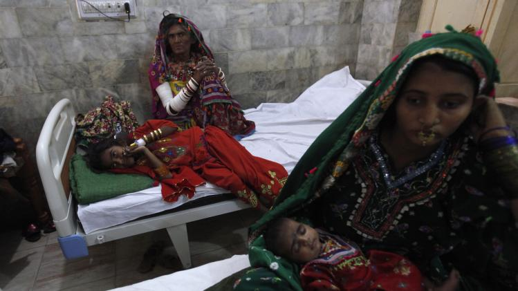Kari, a 9-year-old suffering from a stomach infection, lies beside her mother at the Civil Hospital in Mithi, Sindh province