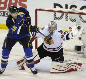Chicago Blackhawks' goalie Corey Crawford, right, makes a glove-save against St. Louis Blues' David Backes (42) during the second period in Game 2 of a first-round NHL hockey playoff series on Saturday, April 19, 2014, in St. Louis. (AP Photo/Bill Boyce)