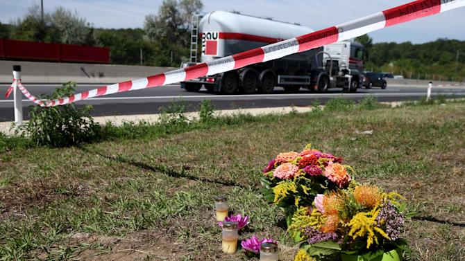 Flowers and candles are placed at the site where a refrigerated truck with decomposing bodies was found by an Austrian motorway patrol near the Hungarian border on Thursday, near Parndorf