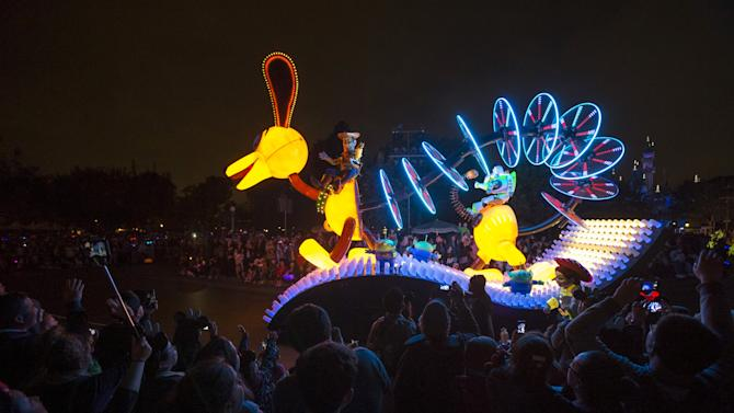 """People watch a float featuring characters from """"Toy Story"""" during the """"Paint the Night - All-New Electrical Parade"""" during Disneyland's Diamond Celebration in Anaheim"""
