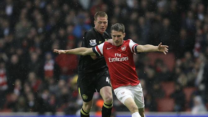 Arsenal's Aaron Ramsey, right, holds the ball away from Wigan Athletic's James McCarthy during their English Premier League soccer match at Arsenal's Emirates stadium in London, Tuesday, May  14, 2013. (AP Photo/Alastair Grant)