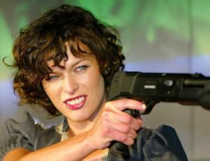 Actress Milla Jovovich poses for a photo with a gun…