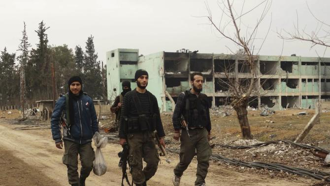 Free Syrian Army fighters walk with weapons at Tameko pharmaceutical factory, after FSA claimed to have taken control of factory, in eastern al-Ghouta, near Damascus