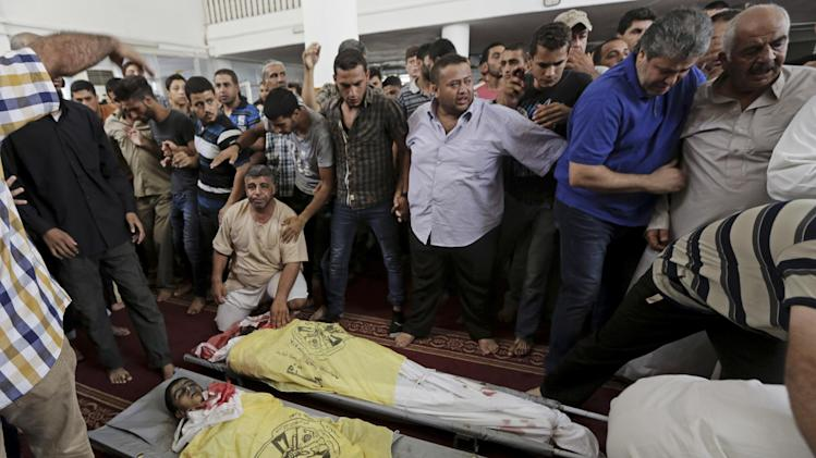 Palestinian relatives gather around bodies of father Nasr al-Rifi, 35, and his child Abdullah, who were killed in Israeli airstrike in their family farm house, during their funeral at a mosque in Gaza in the northern Gaza Strip, Thursday, Aug. 21, 2014. (AP Photo/Adel Hana)