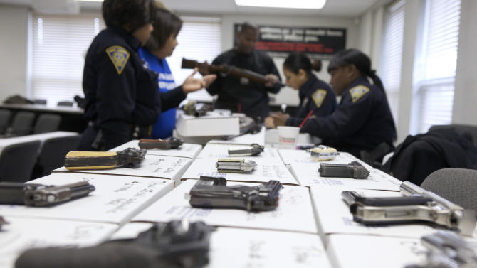 New Haven police officers catalogue guns being turned in during a gun buyback event in New Haven