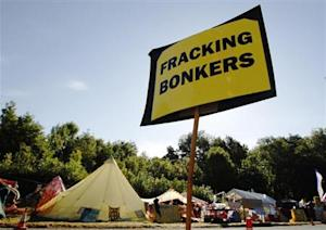 An anti-fracking sign is displayed at the protest camp by the entrance to a site run by Cuadrilla Resources outside the village of Balcombe in southern England
