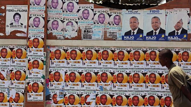 A man walks past a wall covered in posters for election candidates , in the city of Antananarivo, Madagascar, Thursday, Oct. 24, 2013. Madagascar will hold elections on Friday that organizers hope will end political tensions that erupted in a 2009 coup and help lift the aid-dependent country out of poverty. The island nation in the Indian Ocean plunged into turmoil after Andry Rajoelina, the current president, forcibly took power from former President Marc Ravalomanana with the backing of the military. (AP Photo/Schalk van Zuydam)