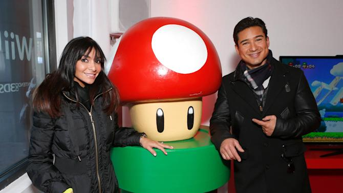 Mario Lopez, left, and Courtney Laine Mazza warm up and check out Wii U at the Nintendo Lounge while playing New Super Mario Bros. U during a break from the Sundance Film Festival on Friday, January 18, 2013 in Park City, UT. (Photo by Todd Williamson/Invision for Nintendo/AP Images)