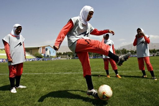 Players of Iran's women national football team warm-up in 2009. Football chiefs agreed on Thursday to lift a ban on women wearing headscarves during games, clearing the way for the participation of many Muslim nations in top-flight competition