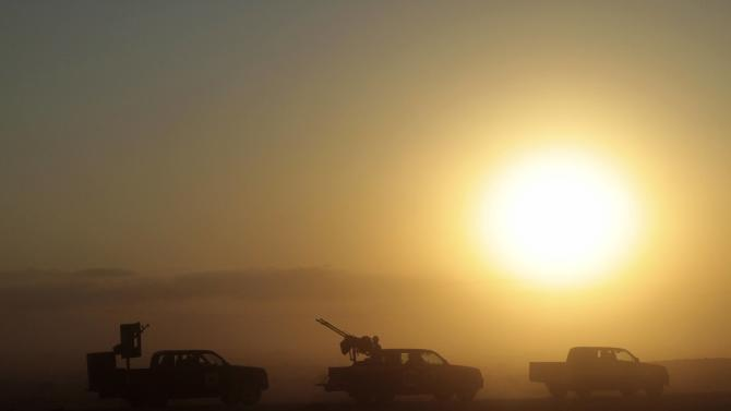 Armed vehicles are seen driving as the sun rises over a desert road leading south out of Misrata, Libya, Sunday, Sept. 11, 2011. The convoy of fighters began a mission to reach and liberate towns that lay between Misrata, Waddan and finality Sirte. Revolutionary forces battled their way back into a key stronghold of Moammar Gadhafi loyalists on Sunday, seizing control of the northern half of Bani Walid and fighting supporters of the fugitive dictator in the town center, said the fighters and a resident. (AP Photo/Gaia Anderson)