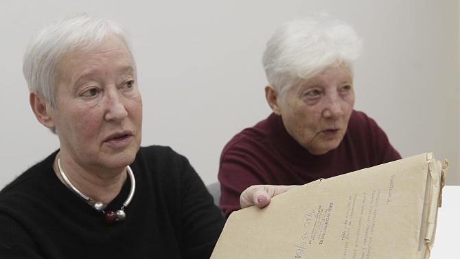 The daughters of Yiddish writer Naftali Herts Kon, Ina Lancman, center, and Vita Serf, right, hold file folders holding Kon's writings that were returned to the daughters on Tuesday, March 5, 2013 and the Warsaw City Archives. The letters, newspaper articles and poems by Naftali Herts Kon, whose real name was Jakub Serf, were deposited with the City of Warsaw Archives by communist authorities after he was sentenced to prison on fabricated charges, in 1963. After 15 months in confinement, Kon left for Israel where he died in 1971. (AP Photo/Czarek Sokolowski)
