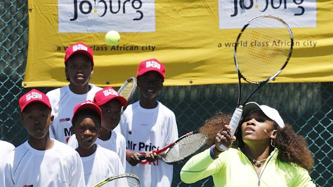 Serena Williams of the United States, right, plays a shot as children look on during their 'Breaking the Mould' development tennis clinic at the Arthur Ashe Academy in Soweto, South Africa, on Saturday Nov. 3, 2012.  Serena and sister Venus arrived in Johannesburg on Saturday and are scheduled to play an exhibition match togehter, as well as conducting some tennis sports clinics for children and adults.(AP Photo/Themba Hadebe)