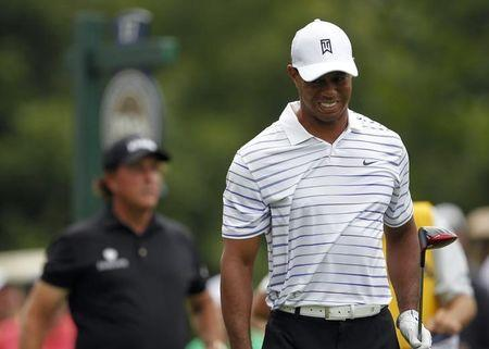 Woods grimaces after his tee shot on the 17th hole as Mickelson looks on during the second round of the PGA Championship at Valhalla Golf Club in Louisville