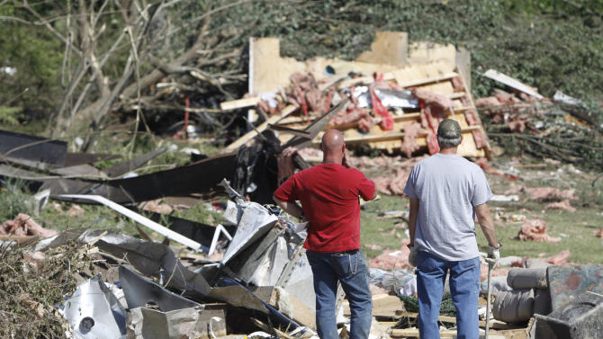 Brad Kidd, left, and Chris Womack stare at what is left of their two mobile homes Friday morning, April 29, 2011, while cleaning up from a fatal tornado that struck DeKalb County, Ala., on Wednesday. DeKalb County incorporates a portion of the 25-mile long path that the twister took. (AP Photo/Chattanooga Times Free Press, Dan Henry) MANDATORY CREDIT