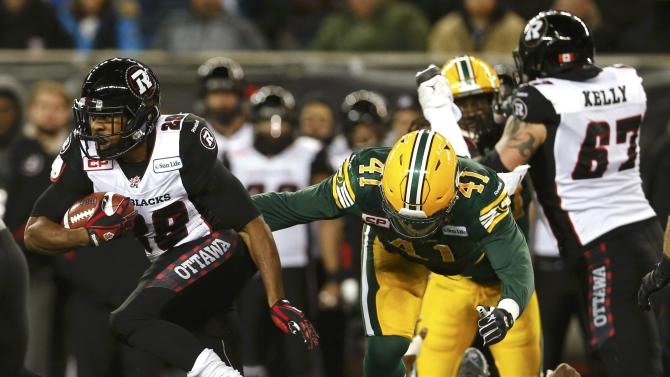 Ottawa Redblacks' William Powell breaks a tackle from Edmonton Eskimos defenders during the first half of the CFL's 103rd Grey Cup championship football game in Winnipeg