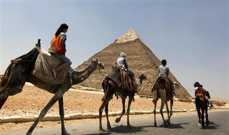 Tourists ride a horse and camels at the Giza Pyramids on the outskirts of Cairo