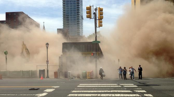 In this photo provided by Jordan McLaughlin, a dust cloud rises as people run from the scene of a building collapse on the edge of downtown Philadelphia on Wednesday, June 5, 2013. A building that was being torn down collapsed with a thunderous boom, raining bricks on a neighboring thrift store, killing a woman and injuring at least 13 other people in an accident that witnesses said was bound to happen. (AP Photo/Jordan McLaughlin)