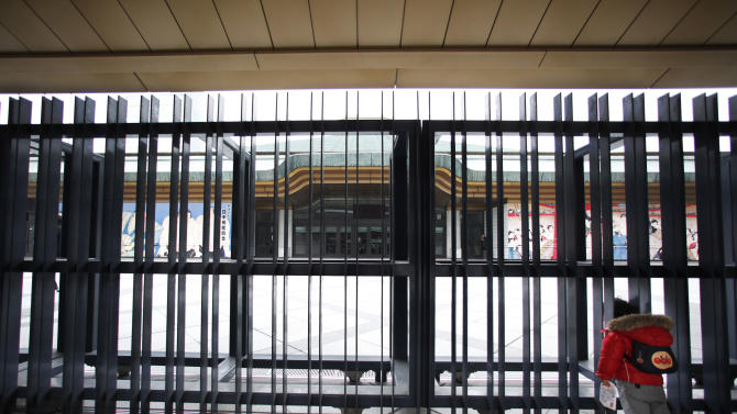 A child peers inside from the gate of Ryogoku Kokugikan sumo arena where the Japan Sumo Association is holding an emergency meeting in Tokyo Sunday, Feb. 6, 2011. In the meeting, the Japan Sumo Association decided to call off its Spring Grand Sumo Tournament scheduled for March, the first cancellation in 65 years, as the country's ancient sport grapples with a match-fixing scandal. (AP Photo/Shizuo Kambayashi)