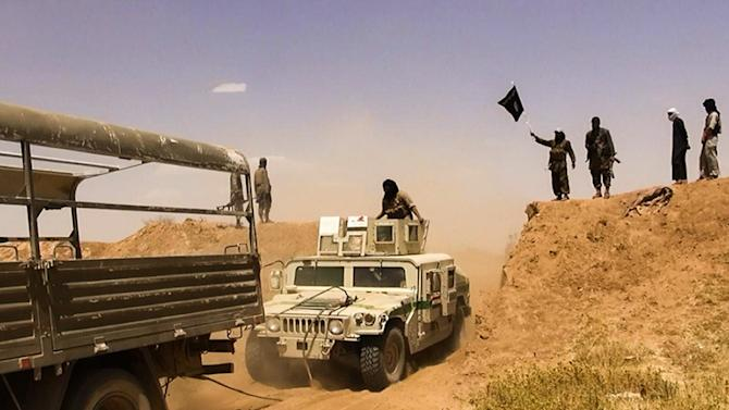 An image made available by the jihadist Twitter account Al-Baraka news on June 9, 2014 allegedly shows Islamic State of Iraq and the Levant militants waving the trademark Jihadits flag in the Syrian-Iraqi border
