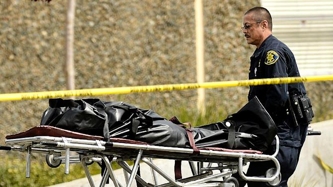 A sheriff's deputy removes a body from outside Oikos University in Oakland, Calif., Monday, April 2, 2012. A gunman opened fire at the Christian university, killing at least seven people and wounding three more, before being captured hours later at a shopping center in a nearby city, authorities said. (AP Photo/Noah Berger)