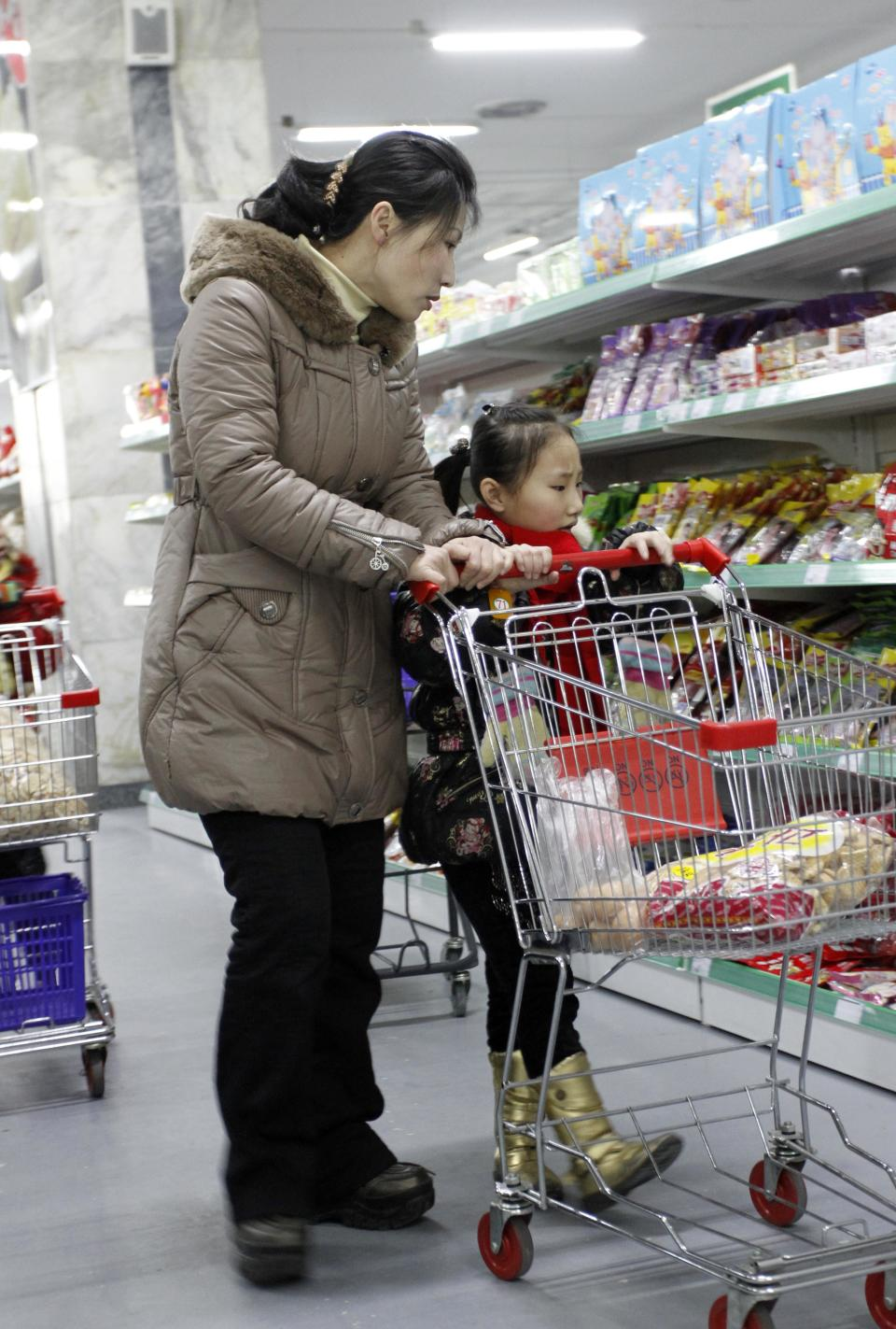 In this Thursday, Jan. 19, 2012 photo, a woman and a young girl push a shopping cart through the Kwangbok Area shopping center as they buy groceries in Pyongyang, North Korea. (AP Photo/Kim Kwang Hyon)