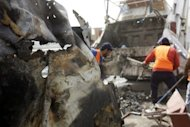 Iraqis remove debris after a blast in central Baghdad as a wave of apparently coordinated bombing and shooting attacks in six different provinces across Iraq killed at least 38 people and wounded more than 150, security officials said