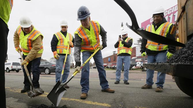 In this Thursday, April 23, 2015 photo, Michigan Gov. Rick Snyder, center, helps patch a pothole on Michigan Ave., in Detroit. Michigan voters will decide the fate of a sales tax increase linked to road improvements because that's what lawmakers proposed after deadlocking on directly raising taxes themselves. But in the months since, legislators have mostly kept quiet on what Gov. Snyder says is the most pressing issue facing the state. Few, in fact, replied to an Associated Press survey asking how they intend to vote on May 5. (AP Photo/Carlos Osorio)