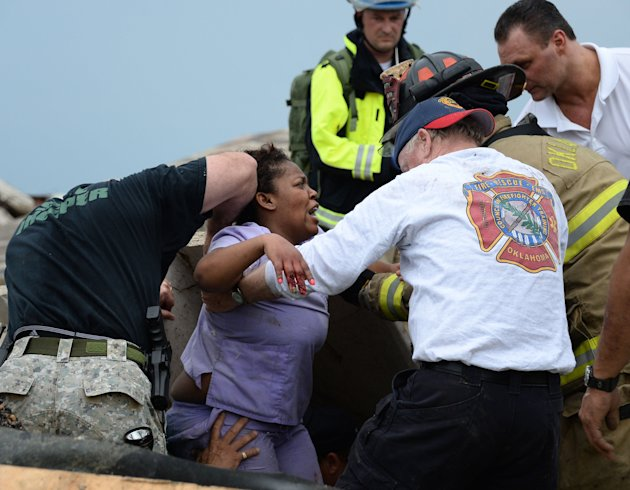 Rescue workers help free one of the 15 people that were trapped at a medical building at the Moore hospital complex in Moore