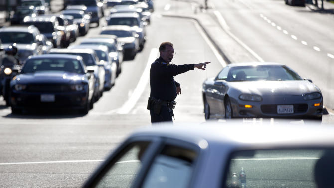 A San Diego police official directs traffic after a power outage Thursday, Sept. 8, 2011, in San Diego. A power outage is affecting millions of people across southern California, Arizona and Mexico. San Diego Gas & Electric Co. Darcel Hulce said that crews Thursday believe the outage was caused by a system breakdown and assured people it was not the result of a terror attack. (AP Photo/Gregory Bull)