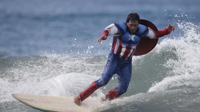 A competitor dressed as Captain America rides a wave during the 7th annual ZJ Boarding House Haunted Heats Halloween surf contest in Santa Monica