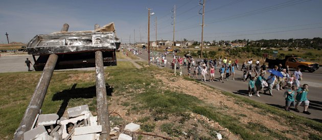 People walk along the path of destruction on the anniversary of a deadly tornado that devastated Joplin, Mo., one year ago on Tuesday, May 22, 2012. The community is marking the anniversary of the twi