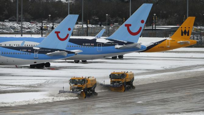 Snow ploughs remove slow from the tarmac at Manchester Airport in Manchester
